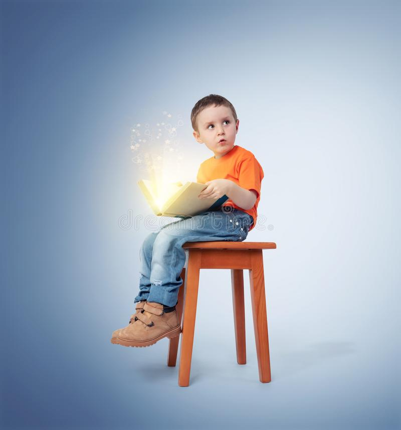 Niño pequeño que se sienta en una silla con un libro mágico abierto, en fondo azul Concepto del cuento de hadas imagenes de archivo
