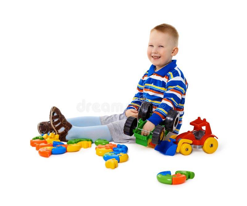 Niño pequeño que se sienta entre los juguetes en suelo imagenes de archivo
