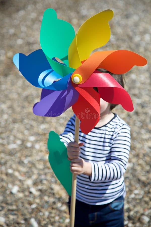 Ni?o peque?o que sostiene el molinillo de viento coloreado foto de archivo libre de regalías