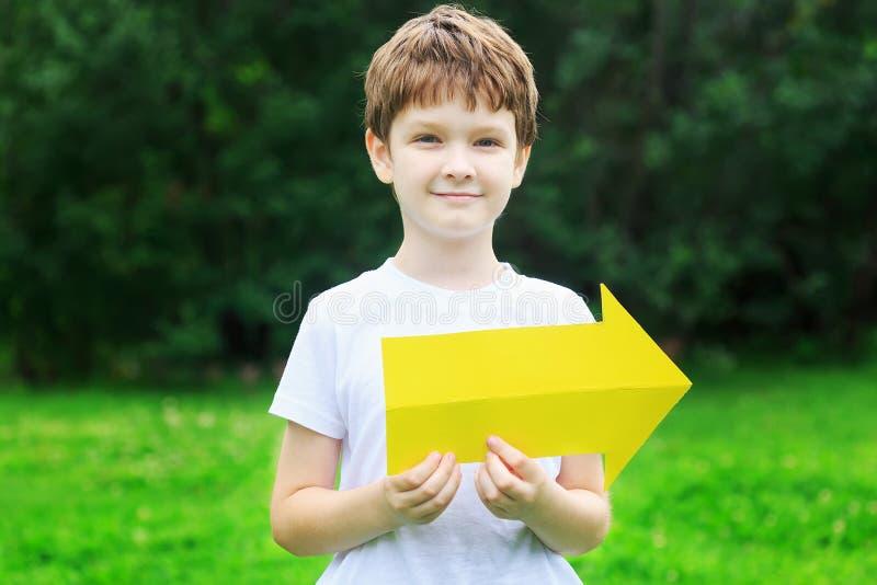 Niño pequeño que sostiene la flecha amarilla en parque del verano imagenes de archivo