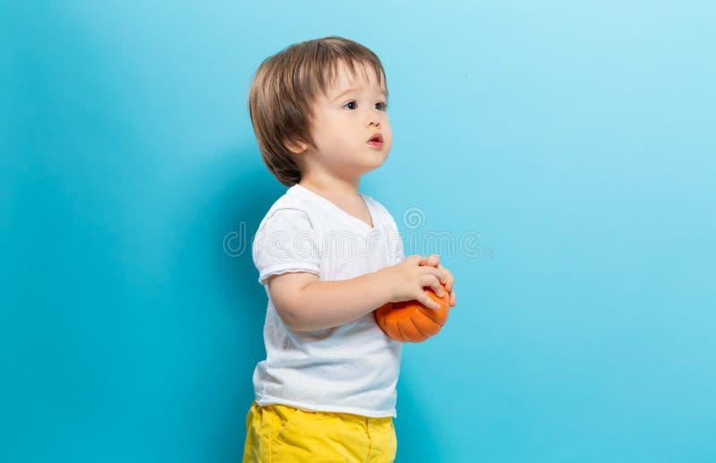 Niño pequeño que sostiene una calabaza para Halloween fotos de archivo
