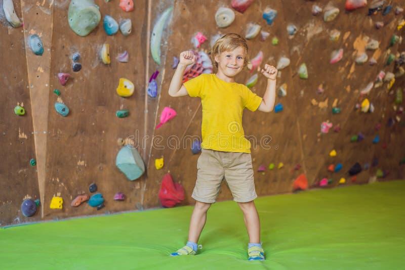 Niño pequeño que sube una pared de la roca en botas especiales indoor imágenes de archivo libres de regalías