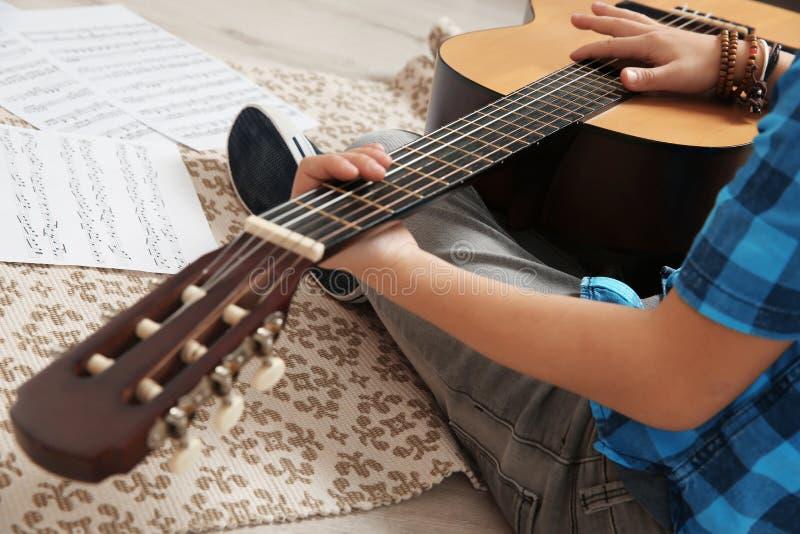 Niño pequeño que toca la guitarra en piso fotos de archivo