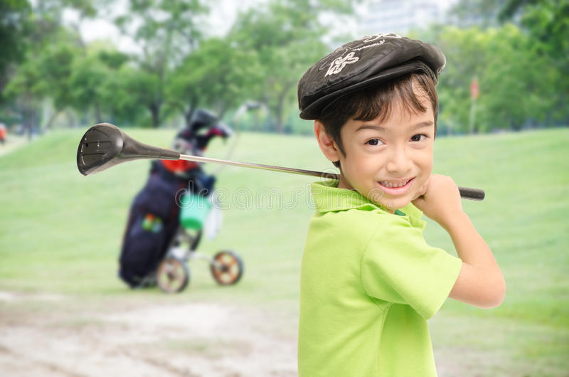 Niño pequeño que toma al club de golf en el fondo blanco imagenes de archivo