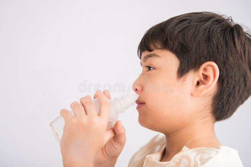 Niño pequeño que usa el agua salada para limpiar su nariz fotografía de archivo