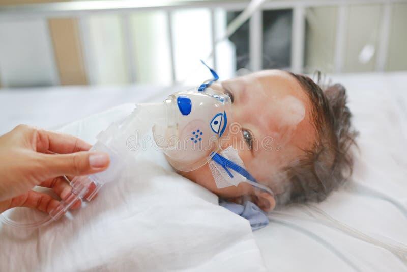 Niño pequeño que usa el nebulizador para curar enfermedad del asma o de la pulmonía El basar enfermo del bebé en pacientes acuest foto de archivo