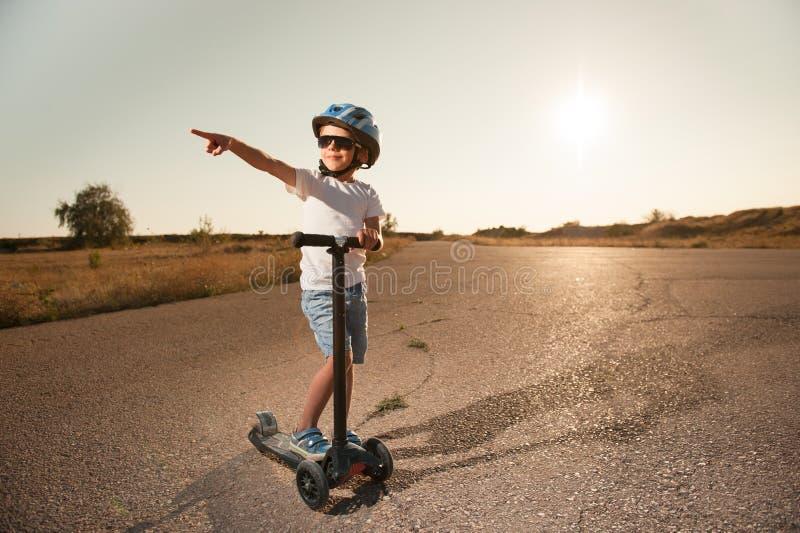 Niño pequeño sano lindo en gafas de sol y casco del deporte con la vespa en el camino imagen de archivo libre de regalías