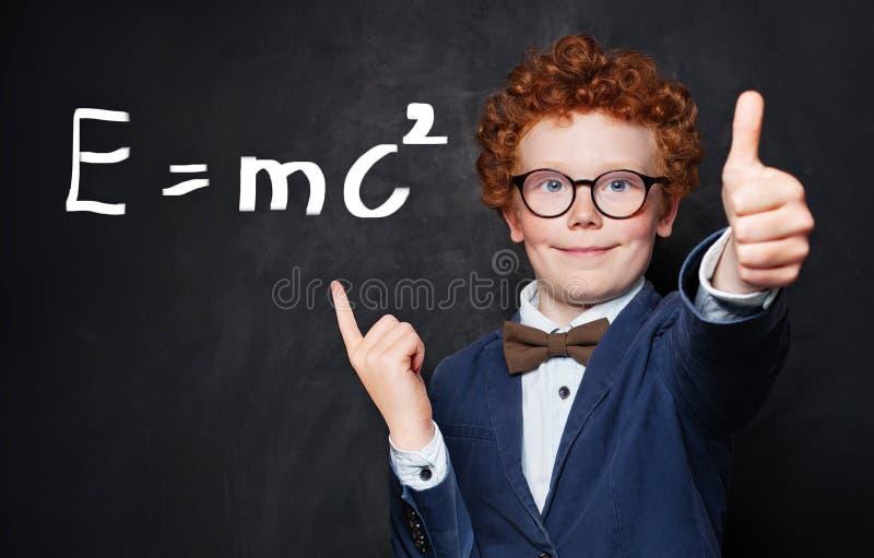Niño pequeño sonriente con el pelo del jengibre que señala en la fórmula de la ciencia en fondo de la pizarra foto de archivo