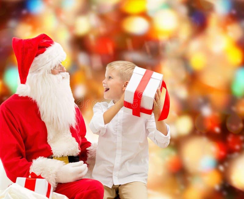 Niño pequeño sonriente con Papá Noel y los regalos imagen de archivo