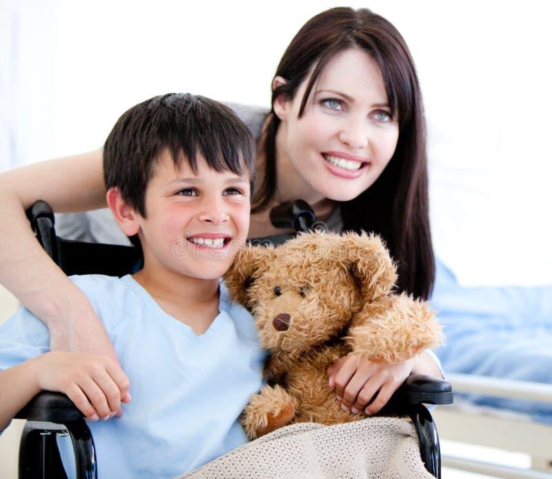 Niño pequeño sonriente en un sillón de ruedas con su madre imagenes de archivo