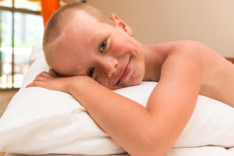 Niño pequeño sonriente feliz que miente en una almohada fotografía de archivo libre de regalías