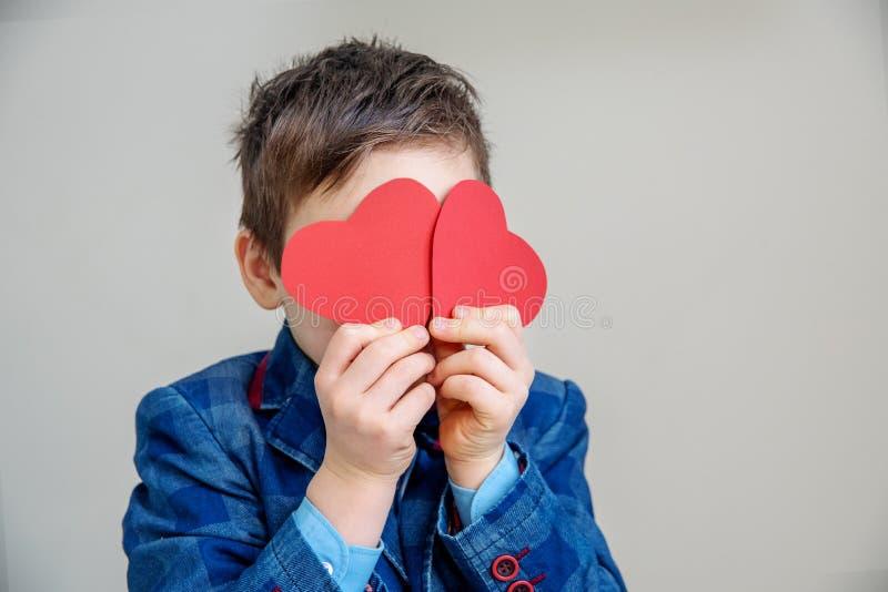 Niño pequeño sonriente lindo en el traje que lleva a cabo corazones rojos en los palillos imagenes de archivo