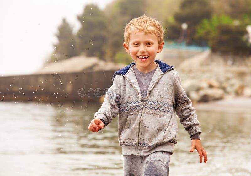 Niño pequeño sonriente lindo funcionado con en descensos del agua imagen de archivo