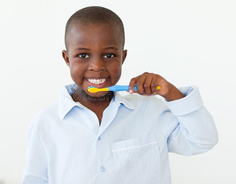 Niño pequeño sonriente que aplica sus dientes con brocha foto de archivo