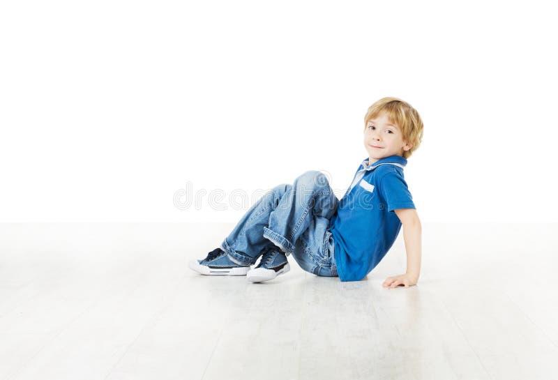 Niño pequeño sonriente que se sienta en el suelo blanco fotografía de archivo libre de regalías