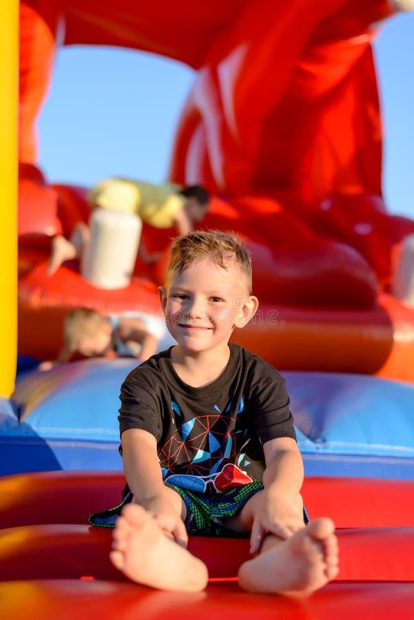 Niño pequeño sonriente que se sienta en un castillo de salto imagen de archivo