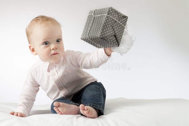 Niño pequeño sorprendido con un presente en la mano El niño infantil pensativo da un presente Bebé alerta fotografía de archivo