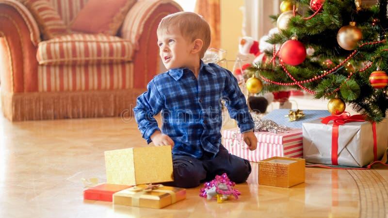 Niño pequeño trastornado que se sienta en piso y que sostiene el regalo de la Navidad foto de archivo