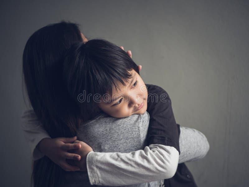 Niño pequeño triste del primer que es abrazado por su madre en casa imagenes de archivo