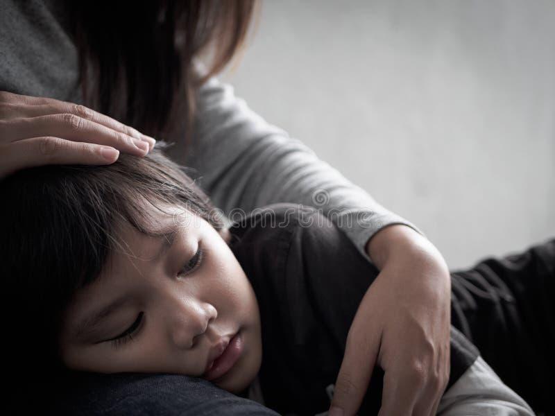 Niño pequeño triste del primer que es abrazado por su madre en casa imágenes de archivo libres de regalías