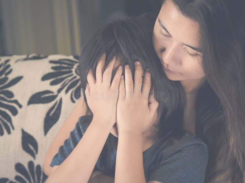 Niño pequeño triste del primer que es abrazado por su madre en casa foto de archivo
