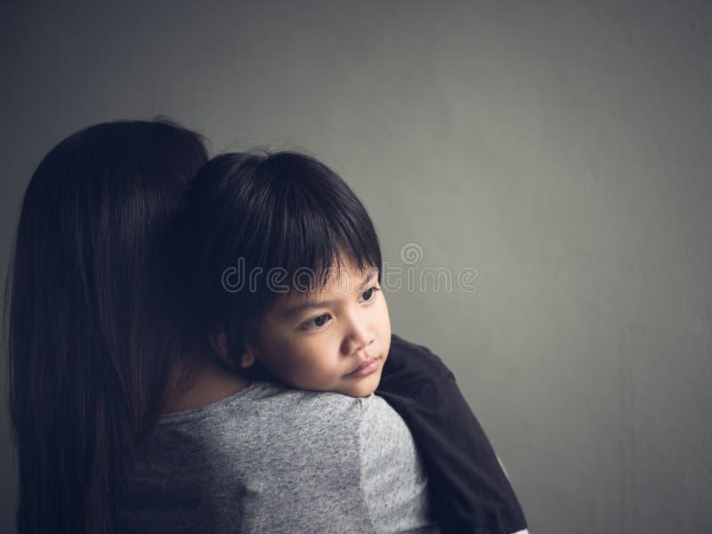 Niño pequeño triste del primer que es abrazado por su madre en casa fotos de archivo