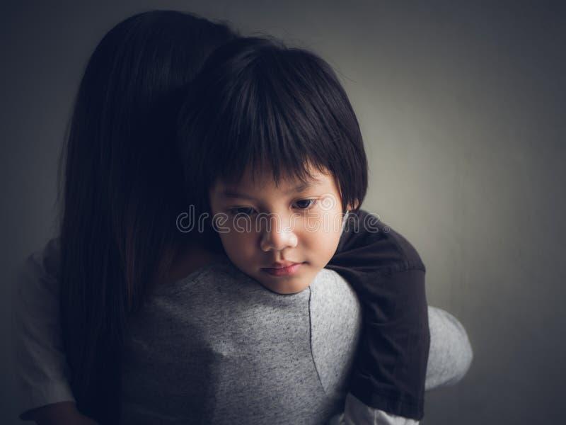 Niño pequeño triste del primer que es abrazado por su madre en casa foto de archivo libre de regalías