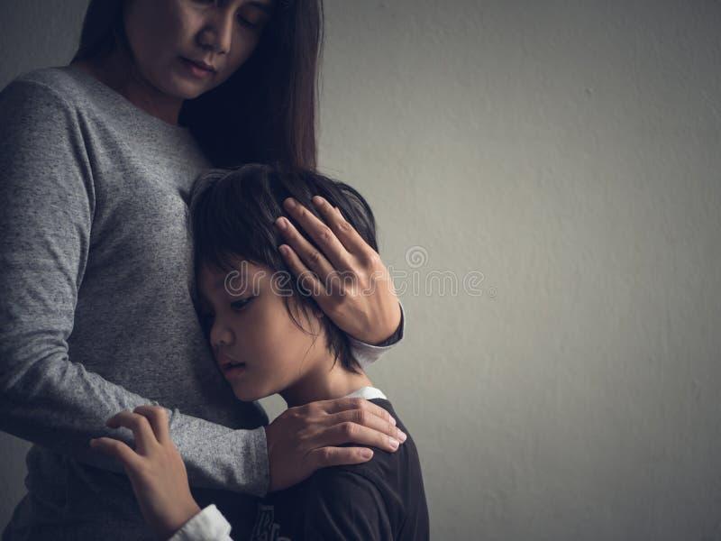 Niño pequeño triste que es abrazado por su madre en casa foto de archivo