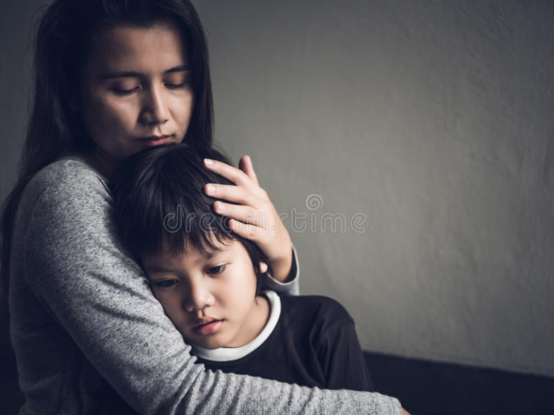Niño pequeño triste que es abrazado por su madre en casa foto de archivo libre de regalías