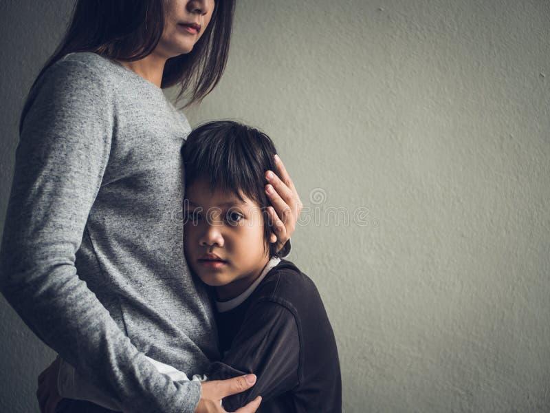 Niño pequeño triste que es abrazado por su madre en casa fotos de archivo