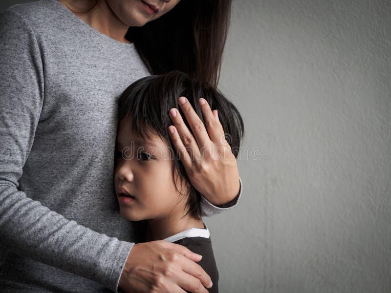 Niño pequeño triste que es abrazado por su madre en casa imagen de archivo