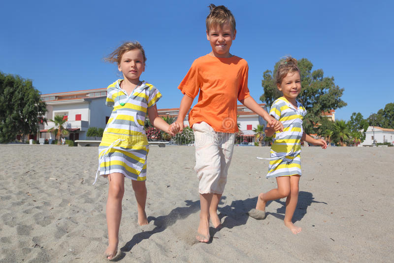 Niño pequeño y dos muchachas que recorren en la playa fotografía de archivo libre de regalías