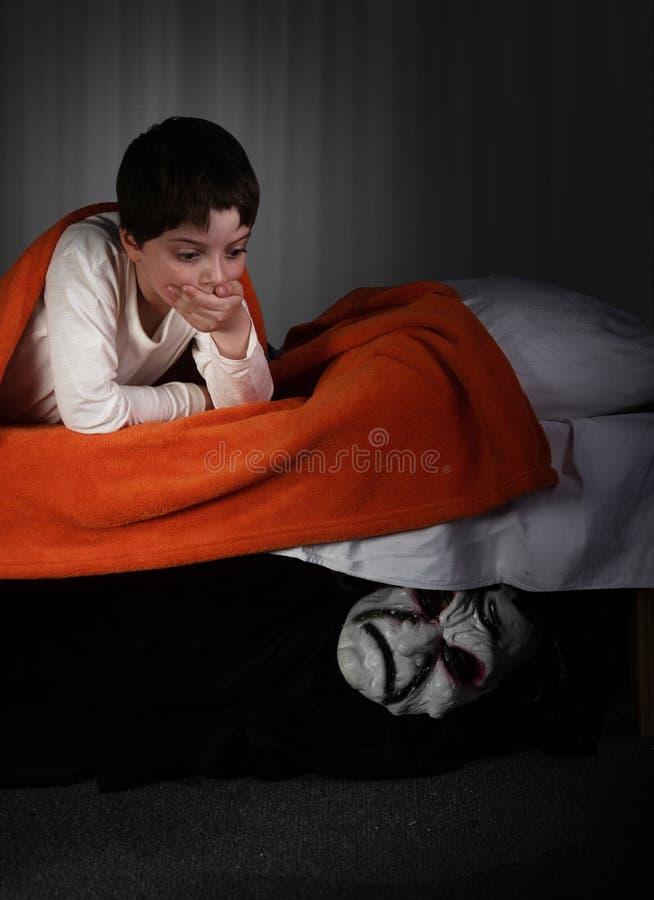 Niño pequeño y monstruo debajo de la cama imágenes de archivo libres de regalías