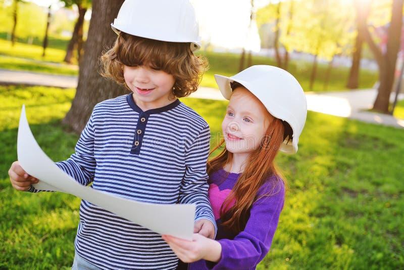 niño pequeño y muchacha en los cascos blancos de la construcción que sonríen mirando el dibujo o la hoja de papel blanca en fondo imagen de archivo libre de regalías
