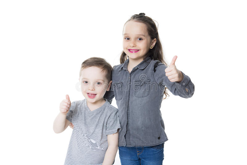 Niño pequeño y muchacha lindos con su pulgar para arriba en el fondo blanco imagen de archivo