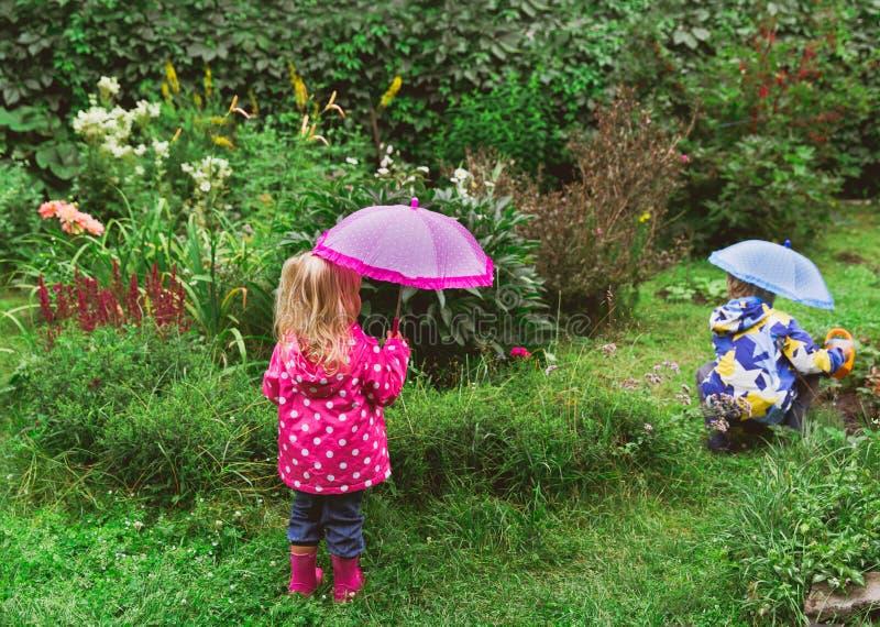 Niño pequeño y muchacha que trabajan en el unter del jardín la lluvia imagenes de archivo