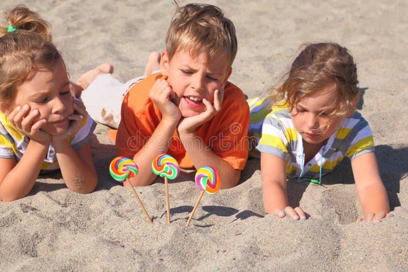 Niño pequeño y muchachas que mienten en la playa imágenes de archivo libres de regalías