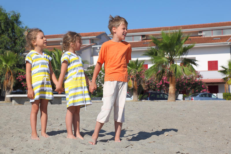 Niño pequeño y muchachas que se colocan en la playa foto de archivo