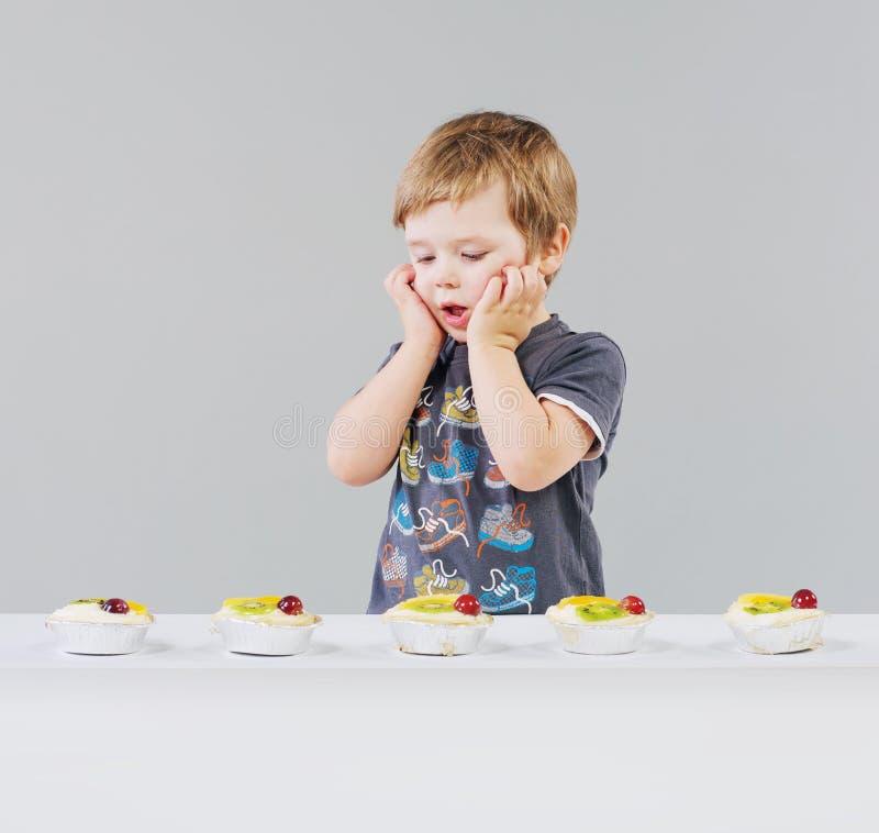 Niño pequeño y muchos dulces foto de archivo