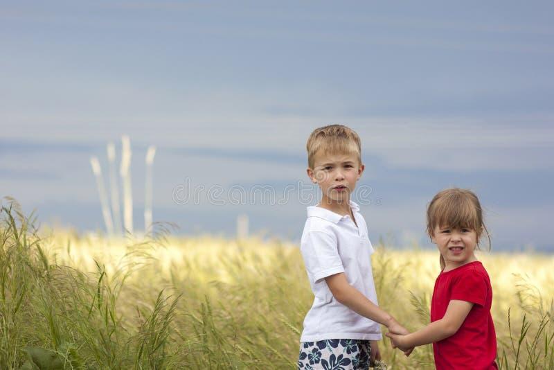 Niño pequeño y niña que se colocan que llevan a cabo las manos que miran en hor imagen de archivo