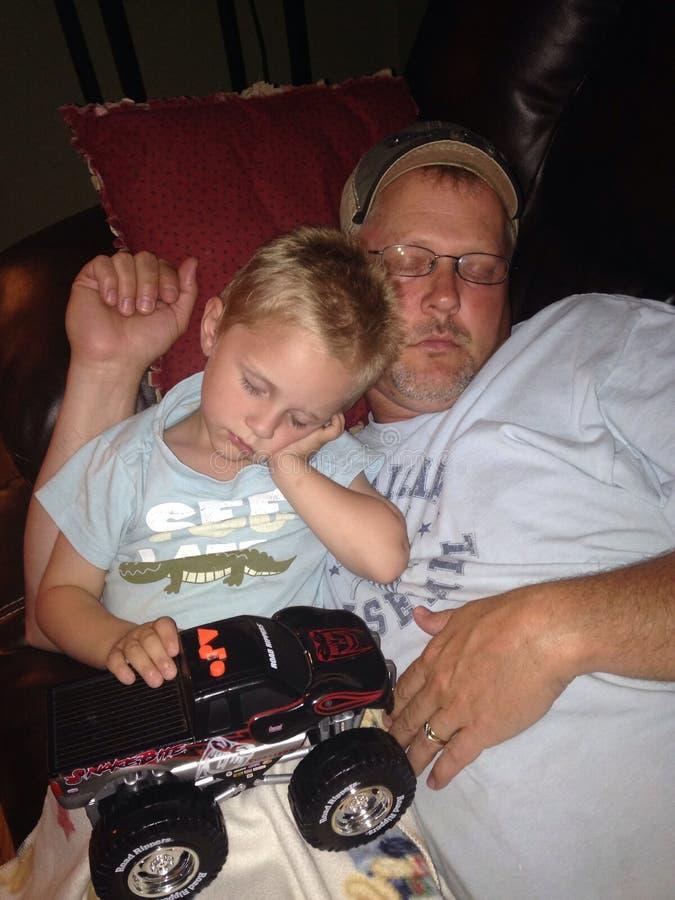 Niño pequeño y papá que duermen junto en el sofá foto de archivo libre de regalías