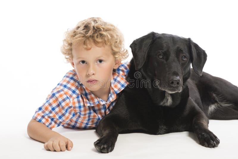 Niño pequeño y perro negro que mienten junto imágenes de archivo libres de regalías