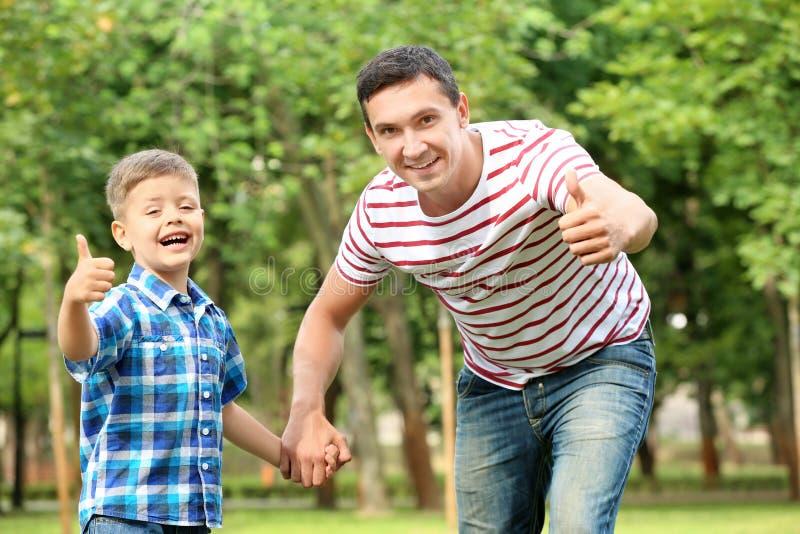 Niño pequeño y su gesto del pulgar-para arriba de la demostración del padre al aire libre imagenes de archivo