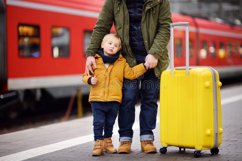 Niño pequeño y su padre que esperan el tren expreso en la plataforma del ferrocarril imagenes de archivo