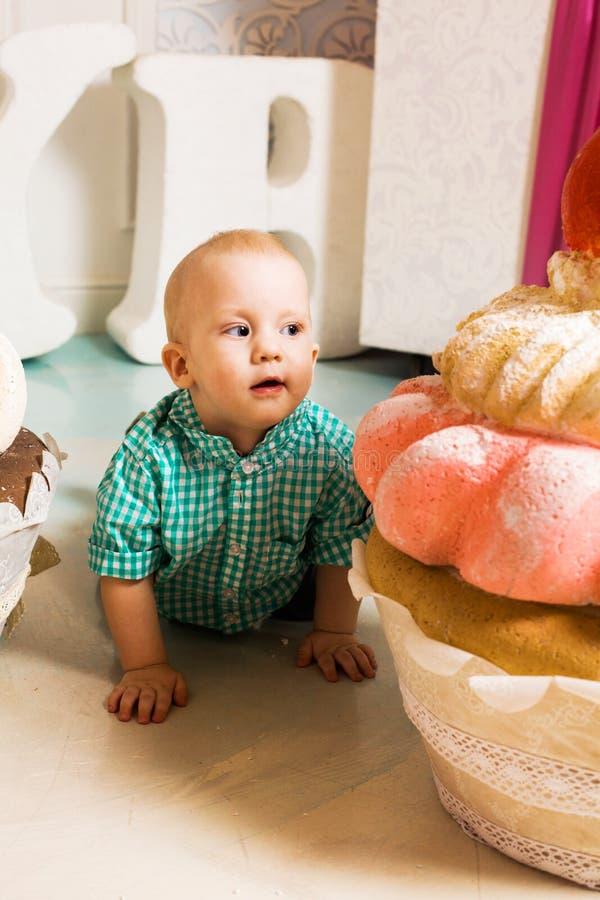 Niño pequeño y torta enorme con las magdalenas de la cereza lindas imagen de archivo