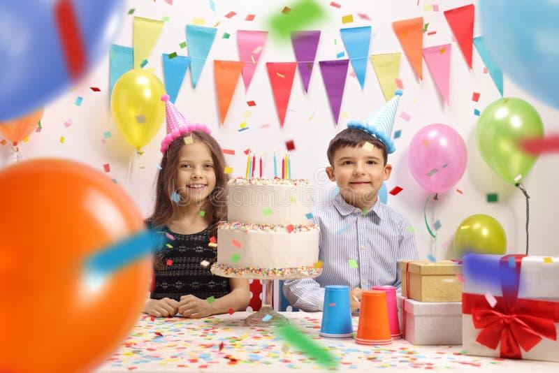 Niño pequeño y una niña que celebra un cumpleaños fotos de archivo