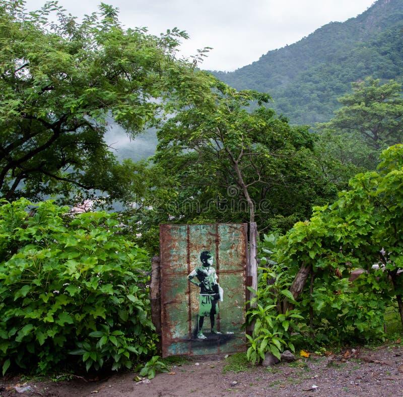 Niño pintado en una puerta oxidada del hierro, en los colores verdes, blancos, negros y marrones que combinan con el fondo verde  imágenes de archivo libres de regalías