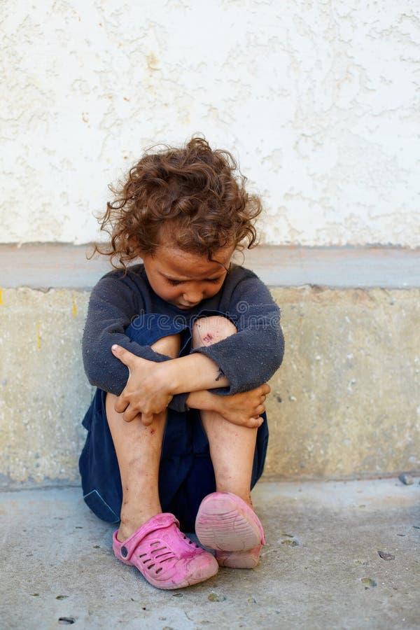 Niño pobre, triste contra el muro de cemento fotografía de archivo libre de regalías