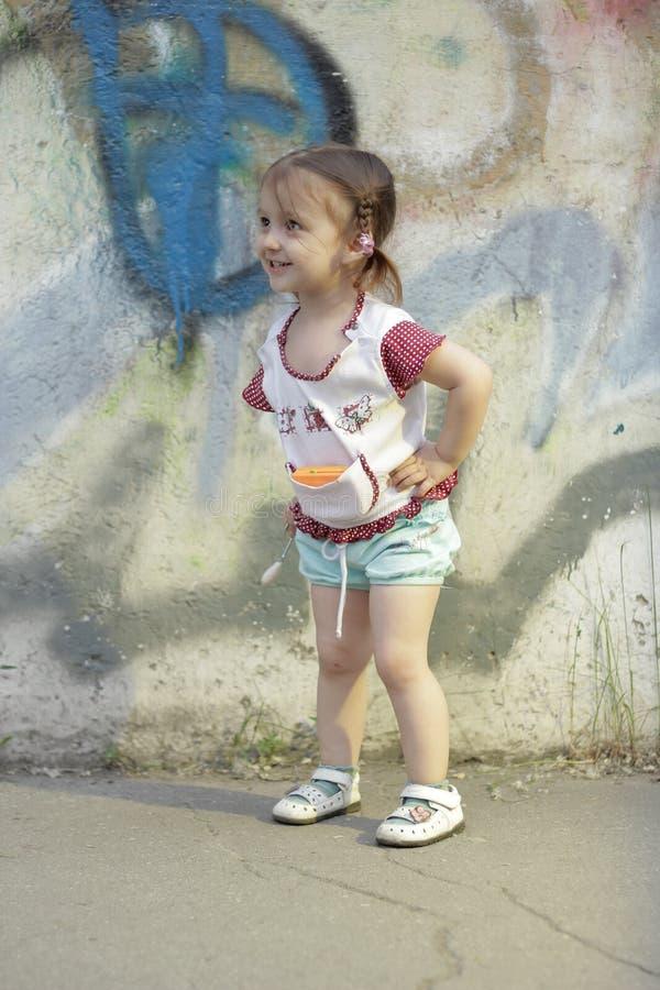 Niño positivo La niña feliz 2-3-4 años con las trenzas en su cabeza, se coloca y sonríe en la calle cerca de un muro de cemento c imagenes de archivo