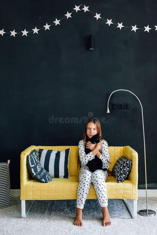 Niño pre adolescente en el sofá contra la pared negra en la vida moderna fotografía de archivo